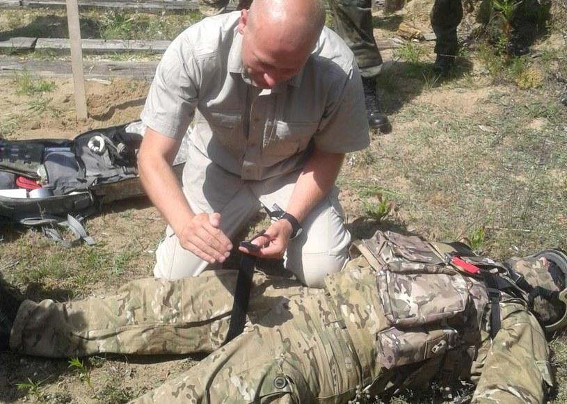 Tomasz Sanak, ratownik z Zakładu Medycyny Pola Walki pokazuje kursantom jak założyć stazę /KBW /INTERIA.PL