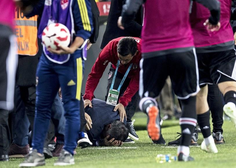 Trener Besiktasu Senol Gunes leży na murawie po ataku kibiców /PAP