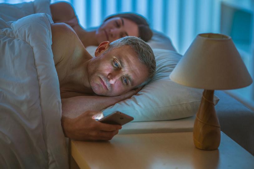 """""""Trochę popatrzę przed snem"""" - korzystanie ze smartfonów tuż przed snem na zły wpływ na nasze samopoczucie, nawet jeśli korzystamy z tak zwanych """"trybów nocnych"""" (filtrów światła niebieskiego) /123RF/PICSEL"""