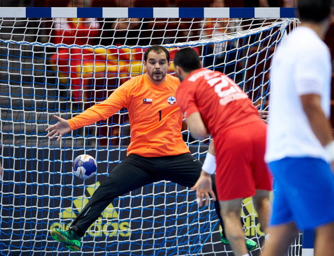 Tunezyjczyk Oussama Boughanmi (C) rzuca na bramkę Chilijczyka Felipe Barrientosa (L) podczas meczu olimpijskiego turnieju kwalifikacyjnego piłkarzy ręcznych w Gdańsku /Adam Warżawa /PAP