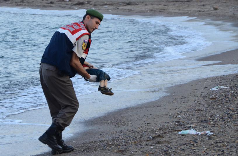 Turecki policjant trzyma ciało trzyletniego Alana Kurdiego /Nilufer Demir / DOGAN NEWS AGENCY / AFP /AFP