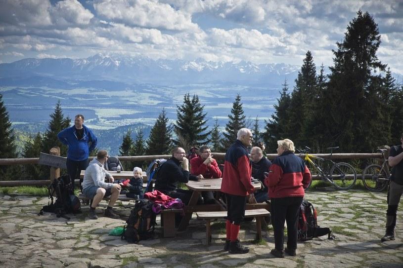 Turyści przed schroniskiem na Turbaczu; w tle panorama Tatr /Dariusz Zarod /East News