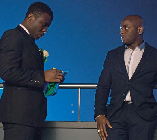 Tuż przed ślubem Kuasi, czarnoskóry przyjaciel Mamutu, wręczy mu flagę Rwandy. /Świat Seriali