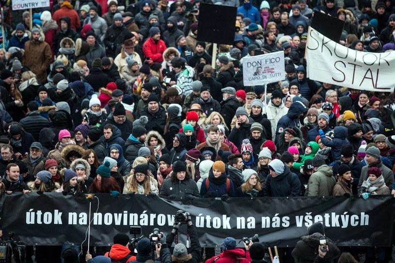 """Uczestnicy marszu trzymają transparent z napisem: """"Atak na dziennikarzy jest atakiem na nas wszystkich"""" /JAKUB GAVLAK /PAP/EPA"""