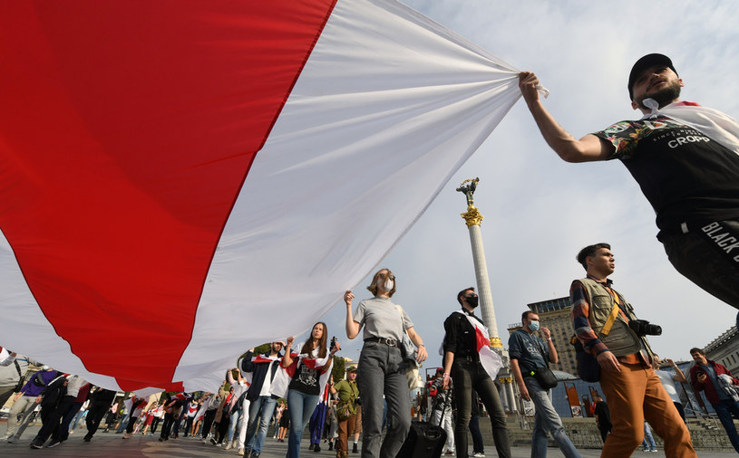 Uczestnicy protestu w Mińsku niosą biało-czerwono-białą flagę, zdjęcie z 4.10.2020 /SERGEI SUPINSKY / AFP /AFP