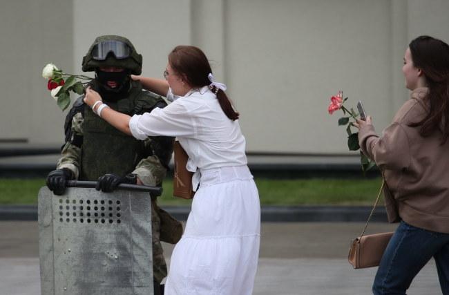 Uczestniczki protestu z kwiatami w rękach pochodzą do żołnierzy /TATYANA ZENKOVICH  /PAP/EPA