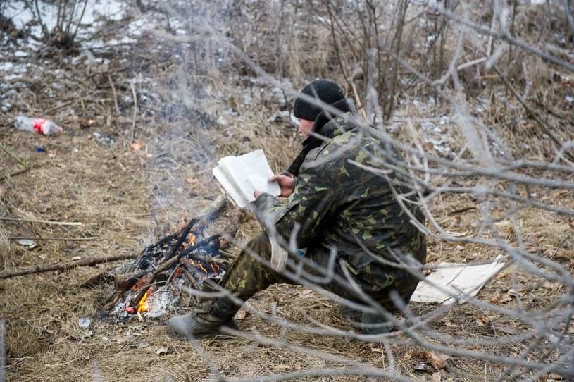 Ukraiński żołnierz czyta książkę podczas postoju na drodze do Debalcewa /AFP