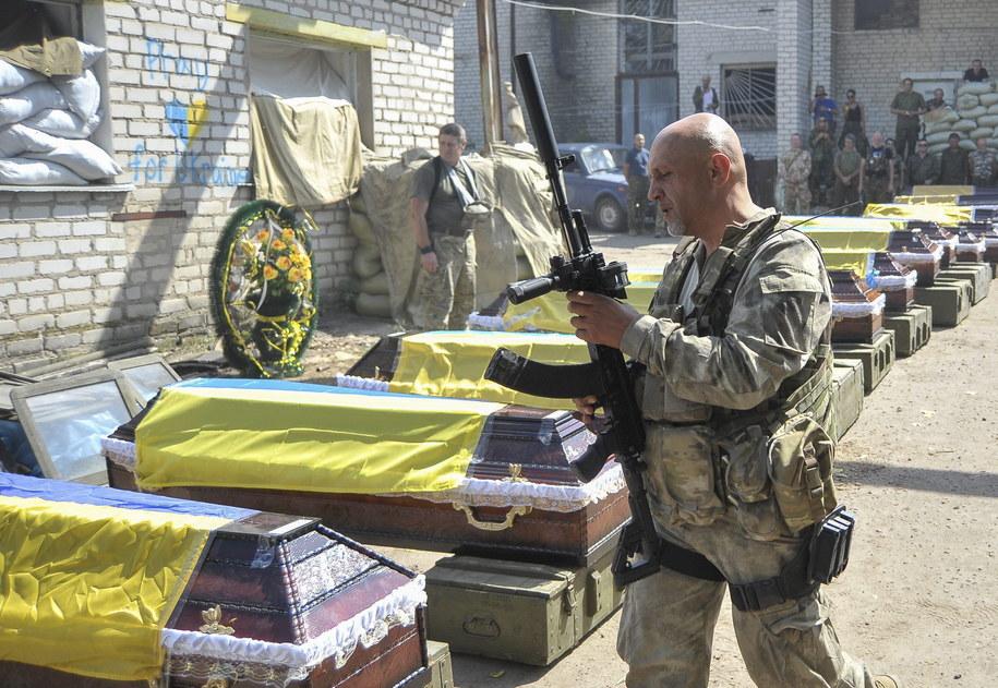 Ukraiński żołnierz oddaje hołd poległym kolegom /IVAN BOBERSKYY /PAP/EPA