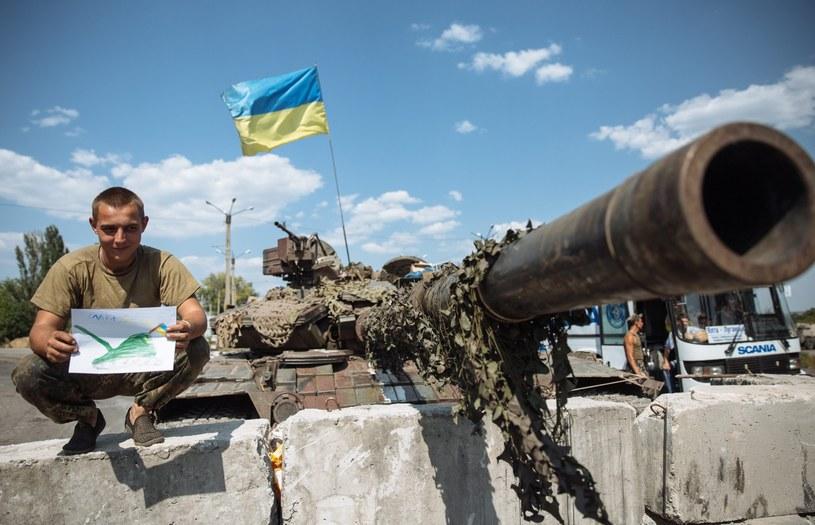 Ukraiński żołnierz pokazuje rysunek, który dostał od dzieci /PAP/EPA
