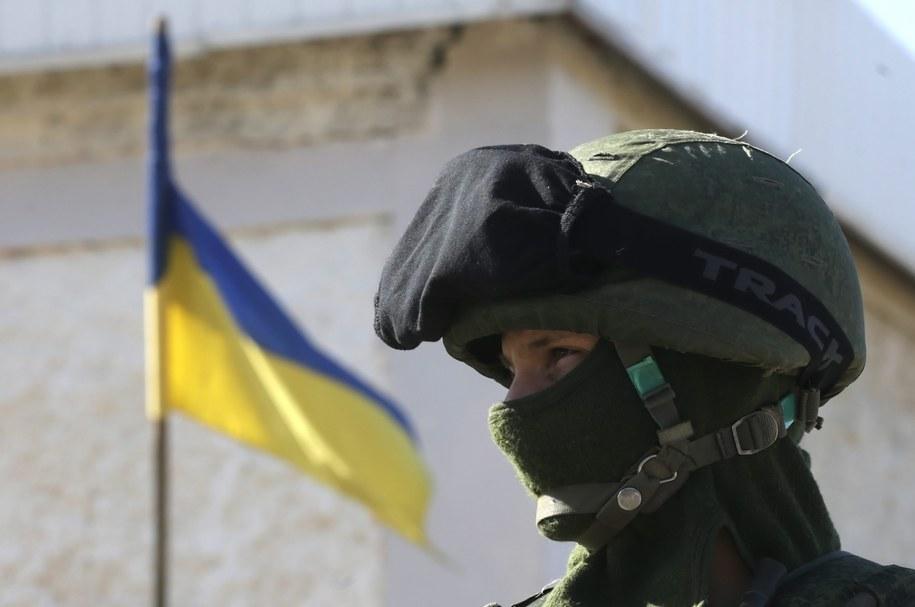 Uzbrojony mężczyzna przed jednostką wojskową na Krymie /MAXIM SHIPENKOV    /PAP/EPA