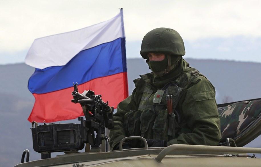 Uzbrojony żołnierz w mundurze bez oznaczeń przed ukraińską bazą w Pierewalnym. W tle rosyjska flaga /YURI KOCHETKOV /PAP/EPA