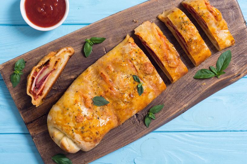 W trakcie pieczenia część farszu wypływa na wierzch pizzy przez zrobione nacięcia /123RF/PICSEL