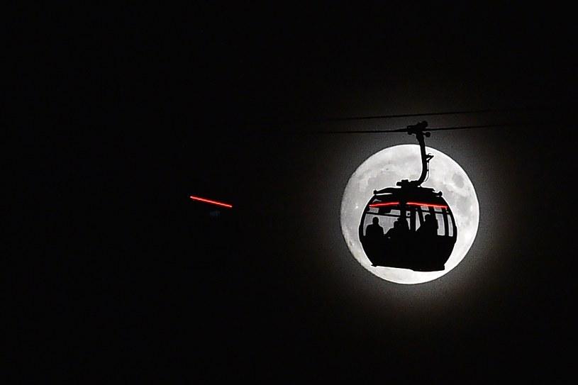 """Wagonik kolei linowej w londyńskim Docklands na tle tzw. """"superksiężyca"""" /GLYN KIRK /AFP"""