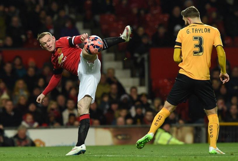 Wayne Rooney w ekwilibrystycznej pozycji, obok Greg Taylor /AFP