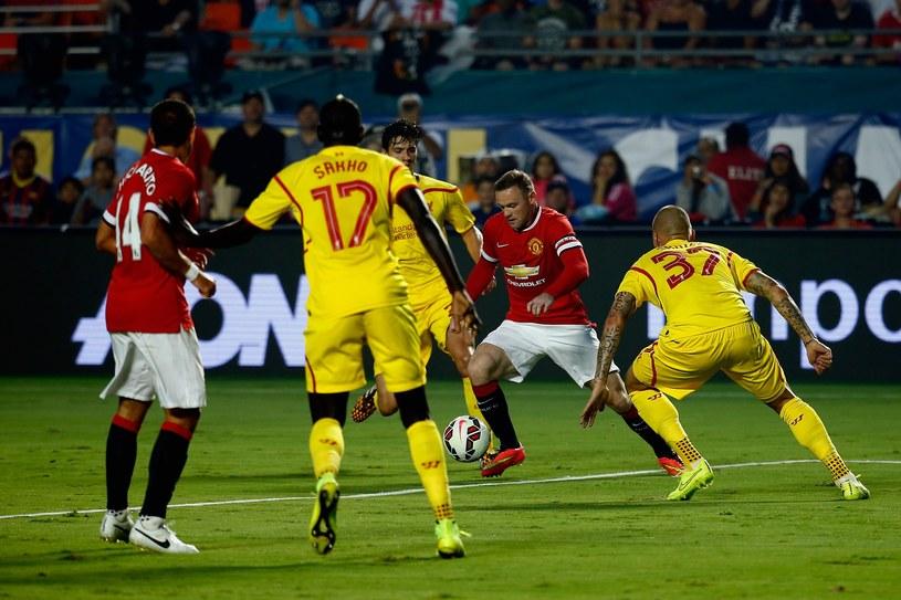 Wayne Rooney w otoczeniu piłkarzy Liverpoolu /AFP
