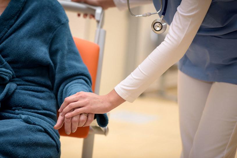 opiekunka trzyma starszą panią za rękę