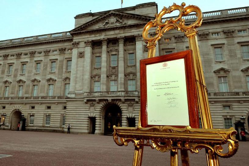 Wiadomość o narodzinach w ramce na ozdobnych sztalugach przez Pałacem Buckingham /AFP