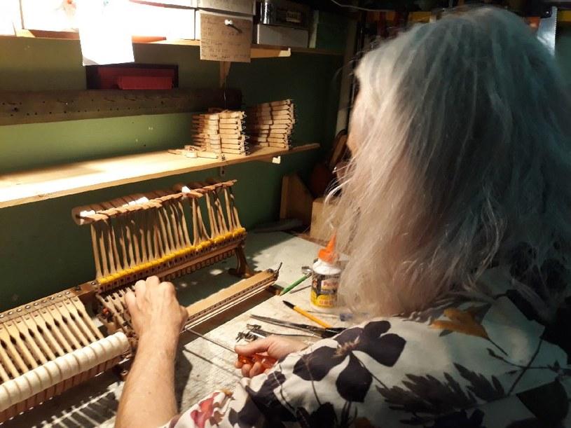 Witold Skoczy remontuje mechanizm pianina. /&nbsp