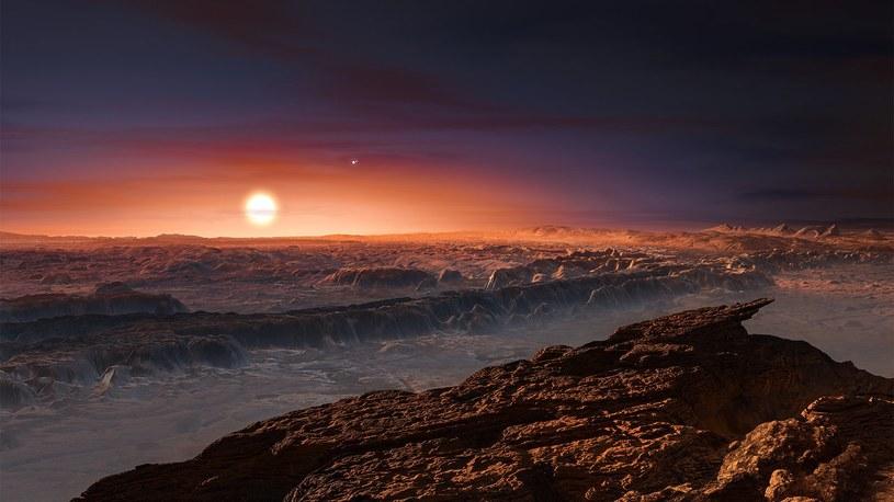 Wizja artystyczna powierzchni planety Proxima b, orbitującej wokół czerwonego karła Proxima Centauri. W tle widoczne pozostałe dwie gwiazdy tego układu wielokrotnego Alfa Centauri AB /materiały prasowe