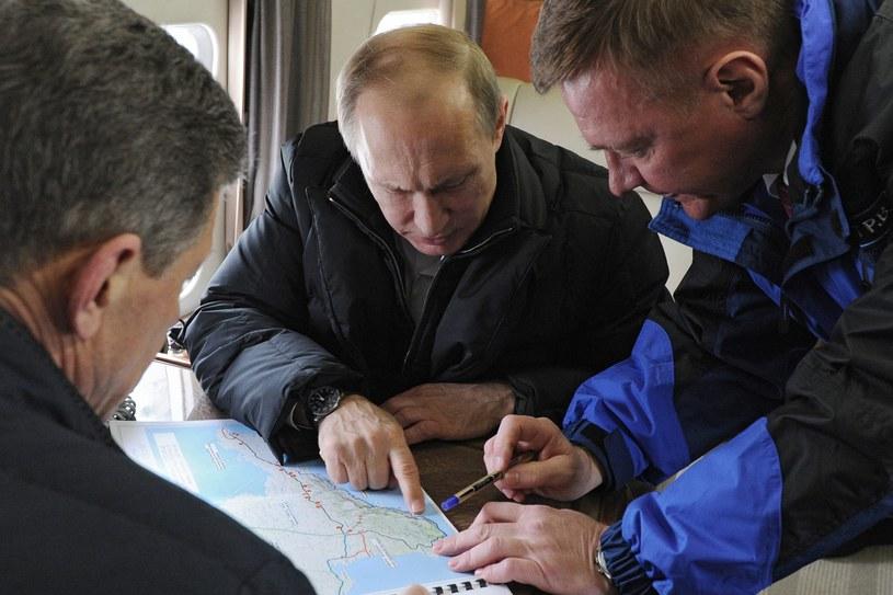 Władimir Putin pochyla się nad mapą Krymu /AFP