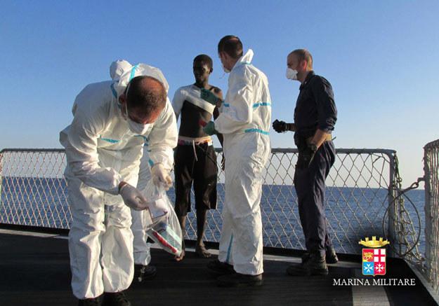 Włoscy medycy udzielają pomocy afrykańskiemu imigrantowi fot. Marina Militare / HO /AFP