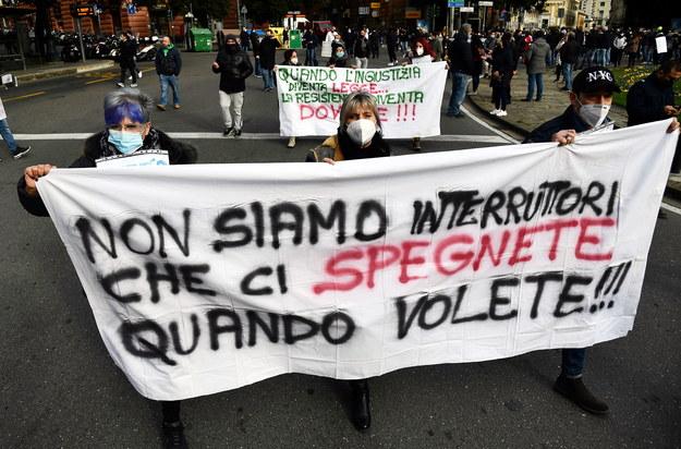 """Włoscy restauratorzy mają dość ograniczeń. Na transparencie napis: """"Nie jesteśmy przełącznikami, które możecie wyłączyć, kiedy chcecie"""" /LUCA ZENNARO /PAP/EPA"""