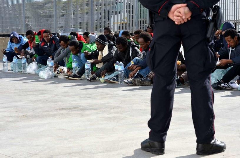 Włoski policjant pilnuje migrantów na Lampedusie /AFP