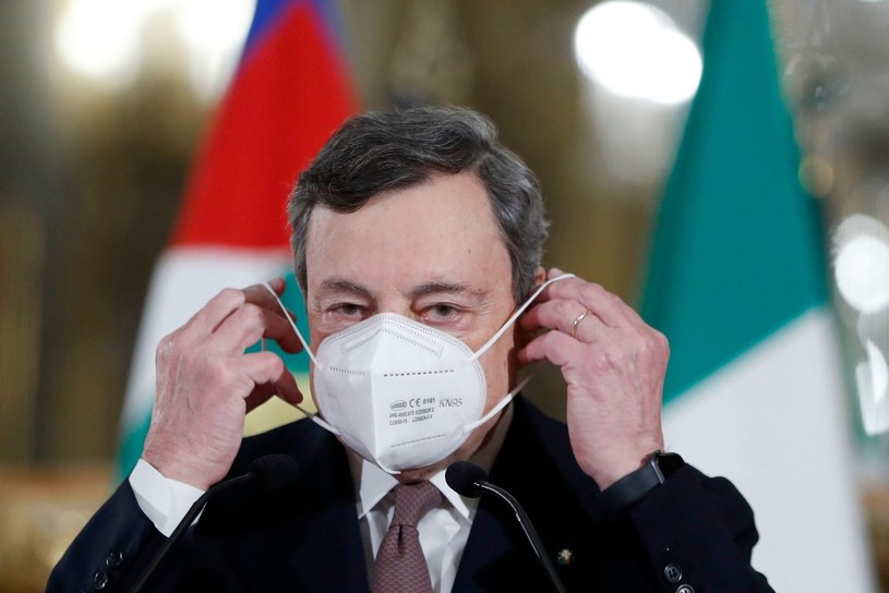 Włoski premier Mario Draghi zakłada maseczkę /AFP