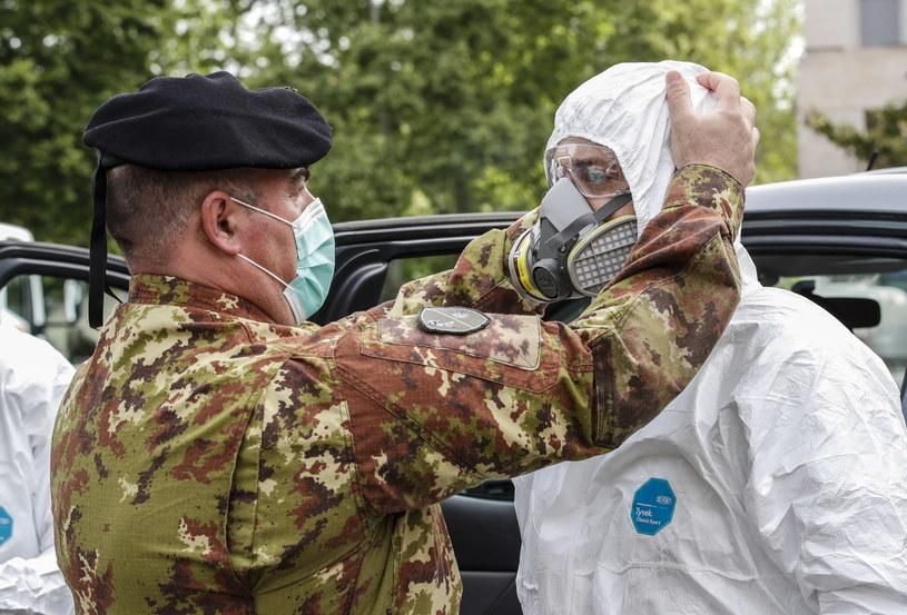 Włoski żołnierz w stroju ochronnym, przygotowujący się do dezynfekcji w czasie pandemii, zdjęcie ilustracyjne /GIUSEPPE LAMI /PAP/EPA