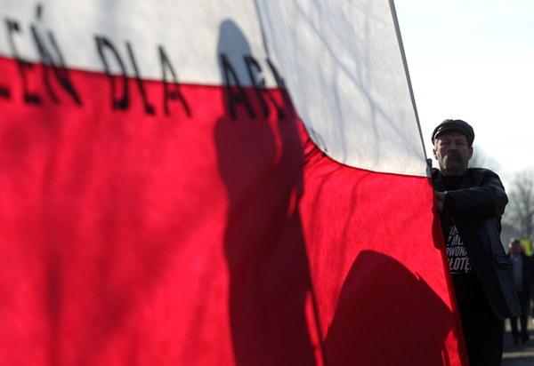 """Polska flaga z napisem """"przestrzeń dla armii wyklętych"""" - akcja performera Jacka Adamasa i środowisk prawicowych podczas uroczystości przed pomnikiem generała Armii Czerwonej Iwana Czerniachowskiego w Pieniężnie"""