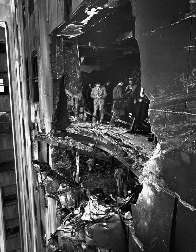Wyrwa, jaką zrobił bombowiec w ścianie wieżowca oglądana przez przedstawicieli pracy /domena publiczna