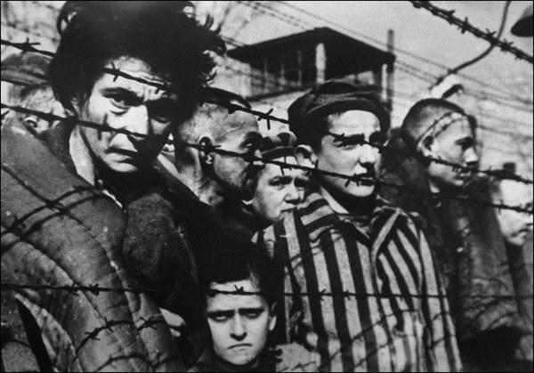 Wyzwolenie Auschwitz - więźniowie za drutami