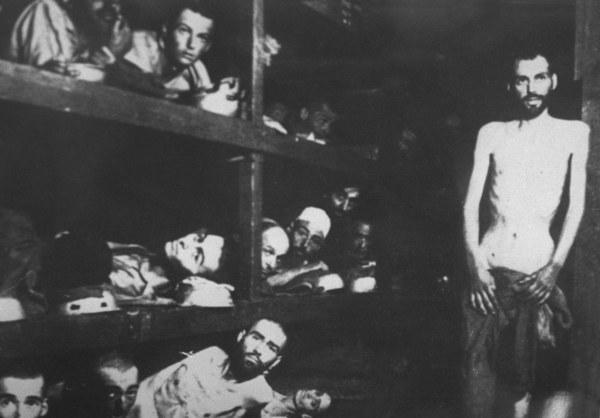 Żydowscy więźniowie w wyzwolonym obozie Auschwitz pozują do zdjęcia radzieckiemu żołnierzowi