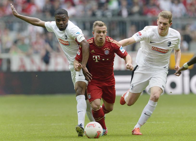 Xherdan Shaqiri otoczony przez piłkarzy Freiburga /AFP