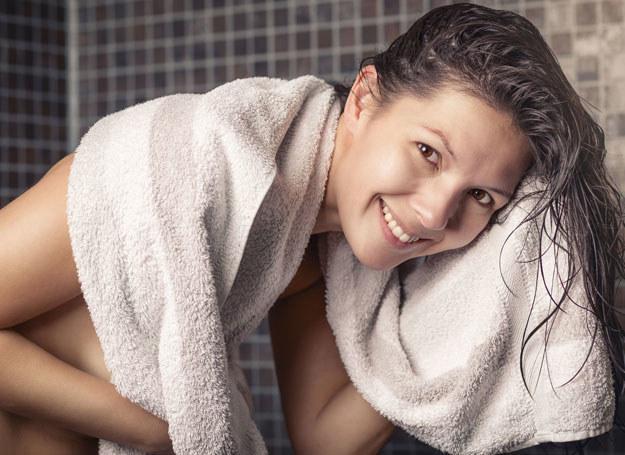 Zanim wysuszysz po myciu włosy ręcznikiem, delikatnie wygnieć je, by usunąć nadmiar wody /123RF/PICSEL