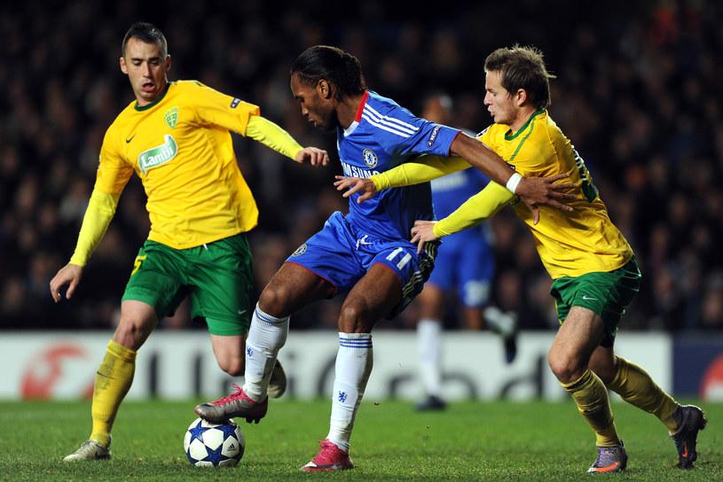 Zawodnicy MSK Żylina próbują zabrać piłkę Didierowi Drogbie z Chelsea podczas meczu Ligi Mistrzów. /ADRIAN DENNIS /AFP