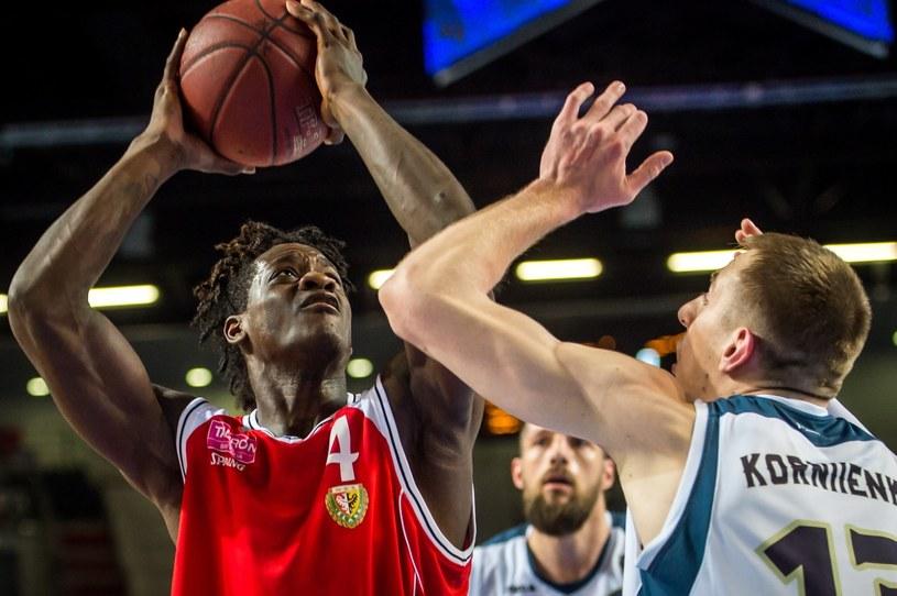 Zawodnik Polskiego Cukru Toruń Maksym Kornijenko (P) blokowany przez Jarvisa Williamsa (L) z WKS Śląsk Wrocław podczas meczu Tauron Basket Ligi /Tytus Żmijewski /PAP