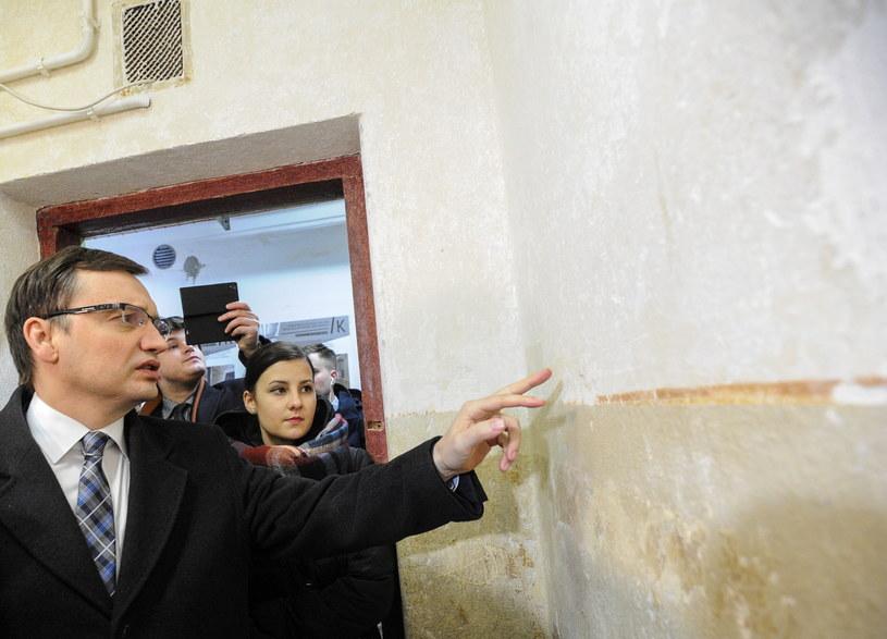 Zbigniew Ziobro wprowadza zwiedzających do piwnic, w których mieścił się areszt  śledczy /Marcin Obara /PAP
