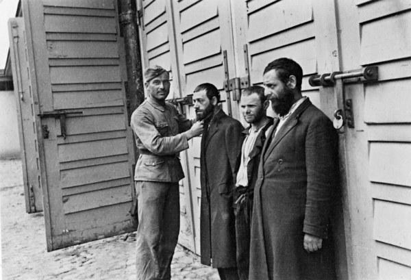 Żołnierz niemiecki ciągnie za brodę jednego z trzech zatrzymanych Żydow. Warszawa, 1939