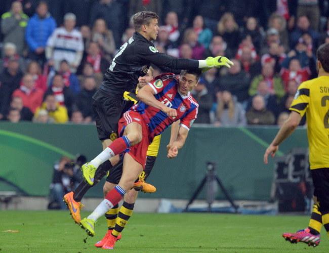 Zderzenie Roberta Lewandowskiego z bramkarzem Borussii Dortmund podczas półfinału Pucharu Niemiec. /PETER KNEFFEL /PAP/EPA