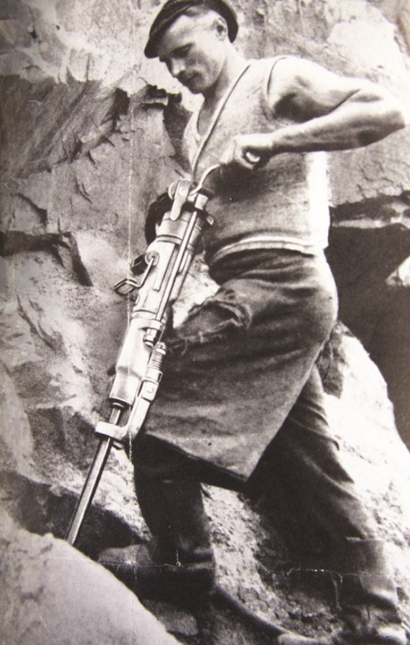 Zdjęcie przedstawia urabianie skały w zboczu góry przy pomocy młota pneumatycznego /Odkrywca