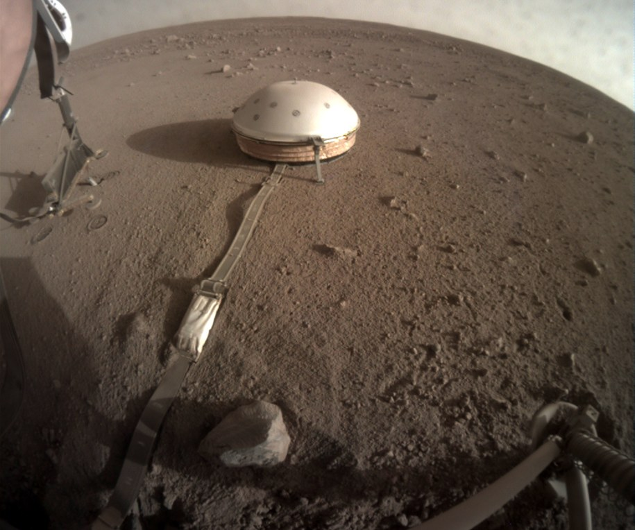 Zdjęcie uniesionej struktury podtrzymujacej (po lewej) i Kreta wbitego w marsjański grunt, wykonane 23.06.2019 roku /NASA/JPL-Caltech /Materiały prasowe