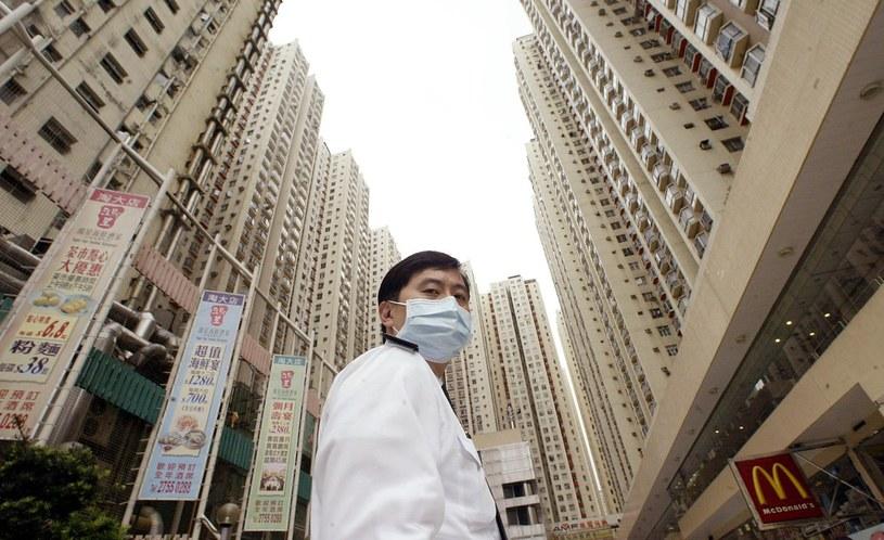 Zdjęcie z 2003 roku przedstawia strażnika z maseczką na twarzy w trakcie pandemii SARS w Chinach. /PETER PARKS /AFP