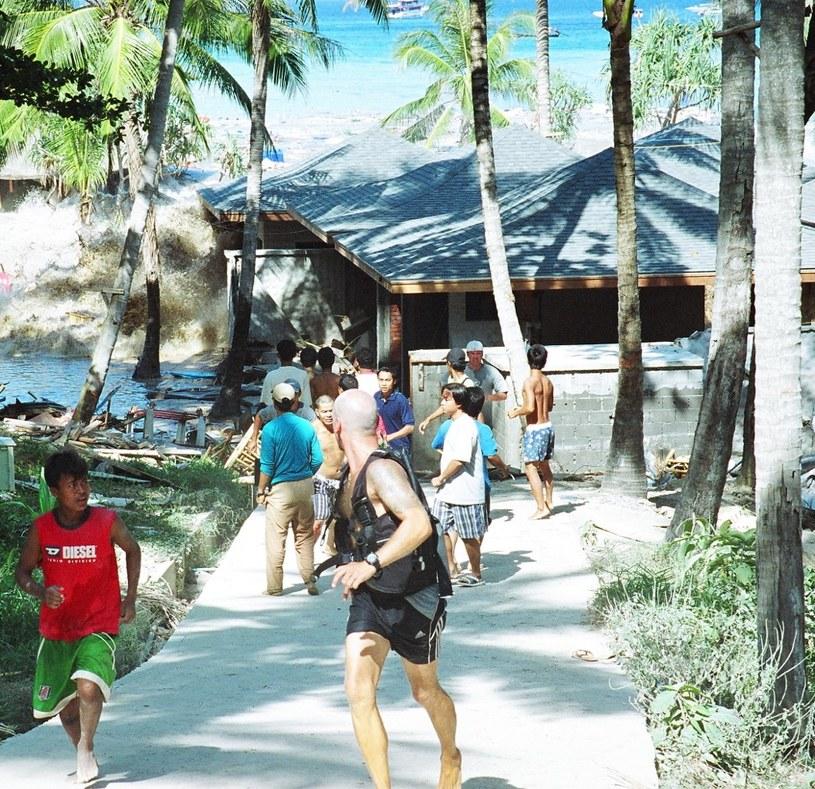 Zdjęcie zrobione 26 grudnia 2004 roku pokazuje ludzi uciekających przed falą tsunami, która rozbija się o brzeg na Koh Raya, części terytorium Tajlandii na Wyspach Andamańskich i tylko ok. 23 kilometry od wyspy Phuket, w południowej Tajlandii /AFP
