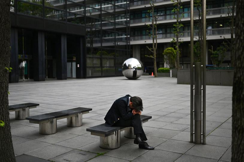 Zmęczony mężczyna na ławce w Tokio, zdjęcie ilustracyjne /CHARLY TRIBALLEAU / AFP /AFP