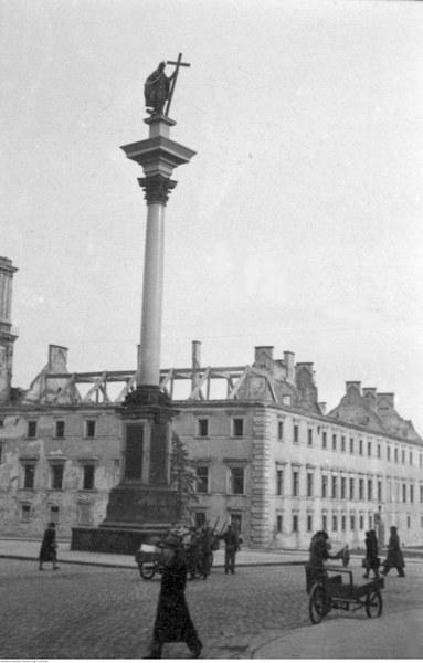 Przechodnie na placu Zamkowym. Widoczny zniszczony Zamek Królewski