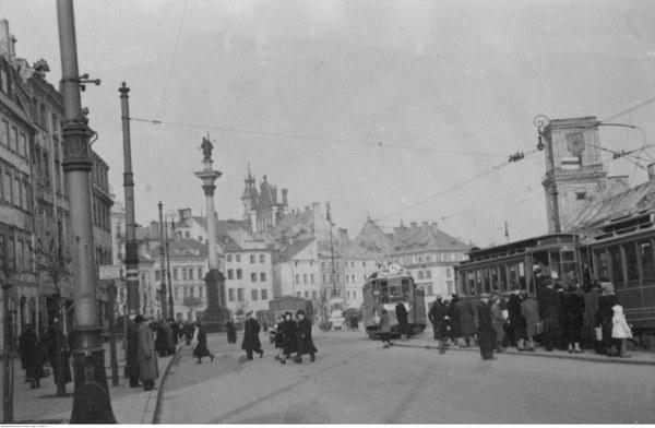 Ruch uliczny na pl. Zamkowym. Widoczny tramwaj nr 5. W tle Kolumna Zygmunta, Stare Miasto i zniszczony Zamek Królewski
