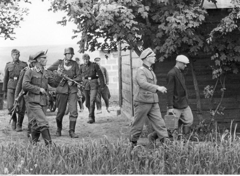 Żołnierze i żandarmi niemieccy podczas przeszukiwania wiejskich zabudowań w czasie wojny (zdjęcie ilustracyjne) /Z archiwum Narodowego Archiwum Cyfrowego