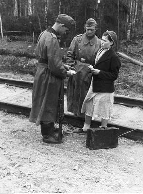 Żołnierze niemieccy podczas kontroli dokumentów radzieckiej kobiety w pobliżu toru kolejowego - przed Leningradem. /Raudies /Ze zbiorów Narodowego Archiwum Cyfrowego