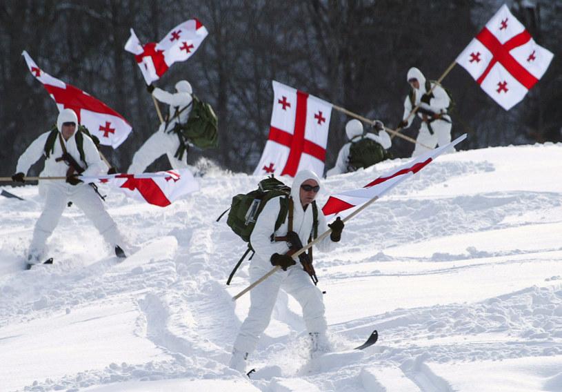 Żołnierze piechoty podczas ćwiczeń w Bakuriani z flagą Gruzji /VANO SHLAMOV /AFP